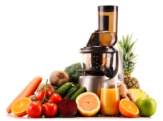 Slow Juicer mit gesundem Obst und Gemüse - bereit um leckeren Saft zu machen